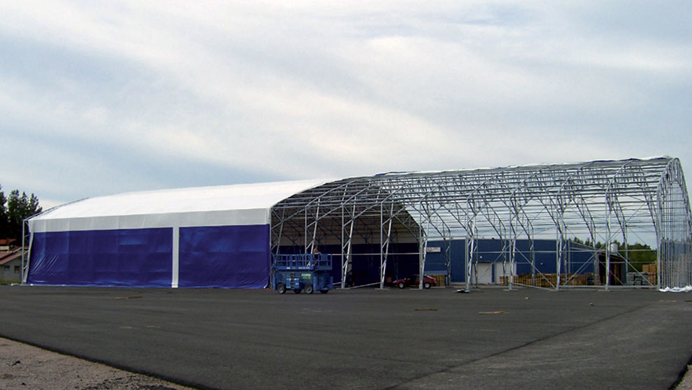 The roof covering of the steel-frame hall is spread out and finally tightened.